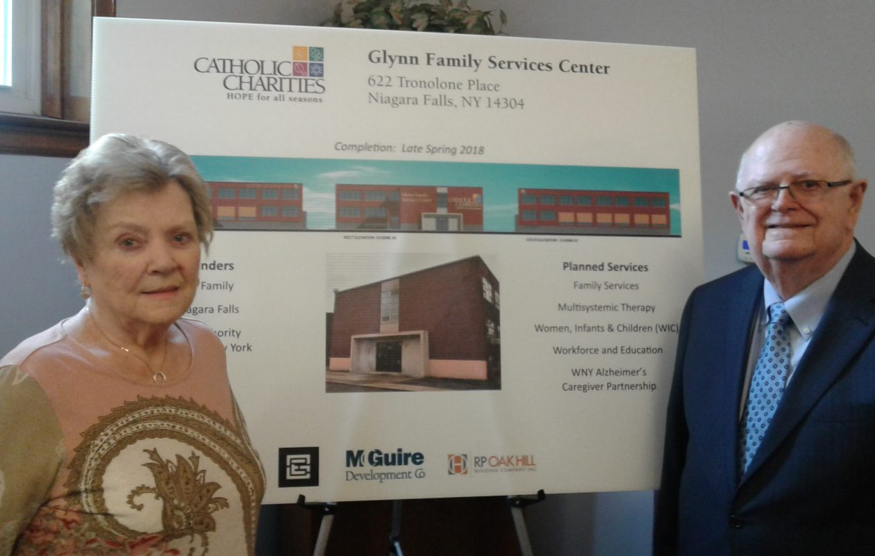 Mary and James Glynn pose with a rendering of Niagara Falls' new Catholic Charities service center on Oct. 30, 2017. (Thomas J. Prohaska/Buffalo News)
