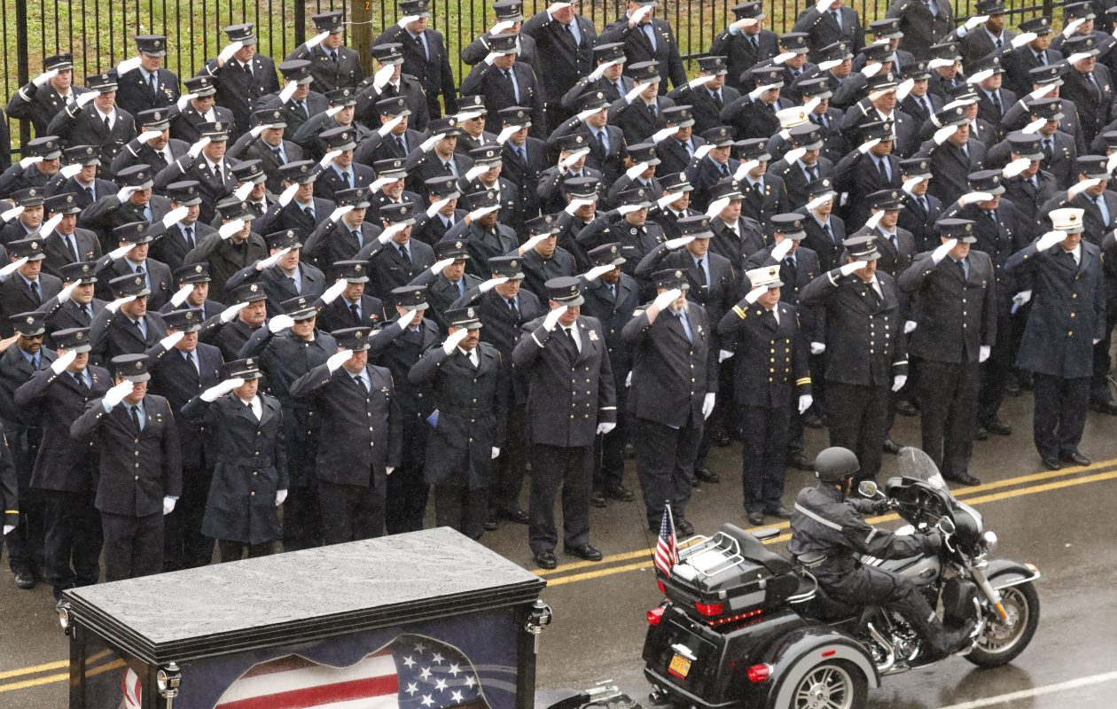 A final salute as the casket of BPD Officer Craig Lehner is pulled by a Harley Davidson hearse past Buffalo Fire Department personnel on Perry Street after funeral services at KeyBank Center, Wednesday, Oct. 25, 2017.  (Derek Gee/Buffalo News)