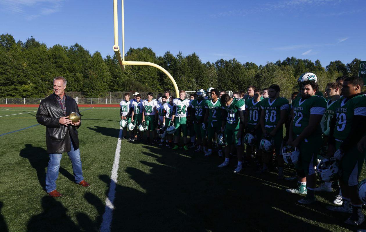 Former Dallas Cowboy Daryl Johnston presents a commemorative Wilson Golden Football to the Lewiston Porter football team after practice on Oct. 1, 2015. (Mark Mulville/Buffalo News)