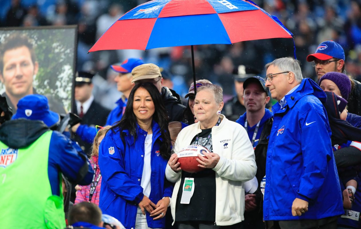 Buffalo Bills owners Kim and Terry Pegula make a presentation to Kathy Lehner, the mother of fallen Buffalo Police officer Craig Lehner, during a tribute before the game. (Harry Scull Jr./Buffalo News)