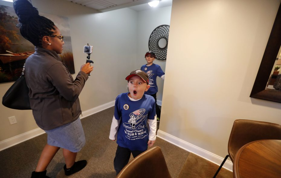 Nathan O'Brien, front, and Jack O'Brien, back, react to seeing the basement in their family's newly renovated home.  (Mark Mulville/Buffalo News)