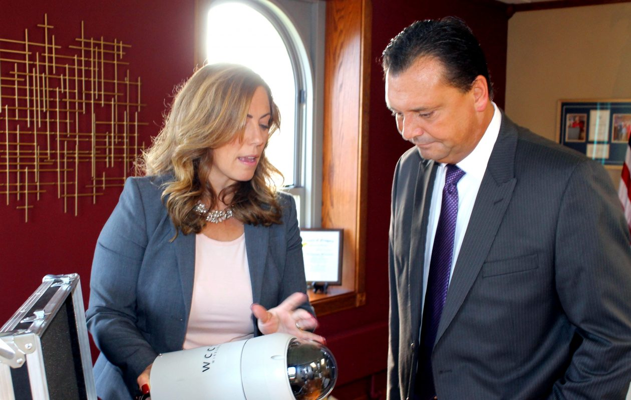 In this photo released by the Niagara County Public Information Office Oct. 10, 2017, District Attorney Caroline A. Wojtaszek shows a new surveillance camera to County Legislature Majority Leader Randy R. Bradt.