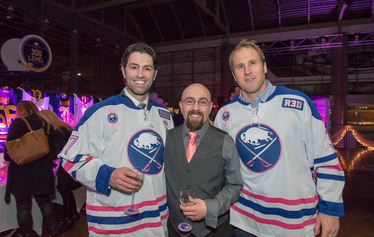 Michael Peca, on the left pictured with a fan and fellow alumnus Matt Ellis at the Sabres Alumni Wine Festival in March, continues to make an impact on the local hockey scene. (Matt Weinberg/Special To The News)