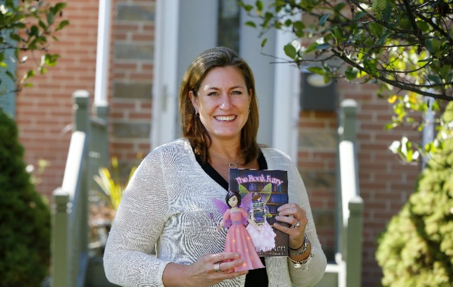 Melanie Bunch holds The Book Fairy book and figurine she created that was inspired by her cousin, Dawn Hochsprung, the Sandy Hook Elementary School principal who dressed as a book fairy to encourage reading before she was killed in the 2012 massacre. (Mark Mulville/Buffalo News)