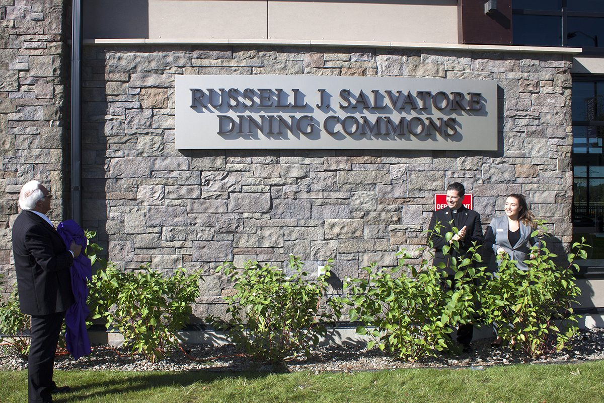 Russell J. Salvatore checks out the new sign on the Niagara University dining facility while Rev. James J. Maher, NU president, and NU senior Sophia Castro look on. (Photo courtesy of Niagara University)