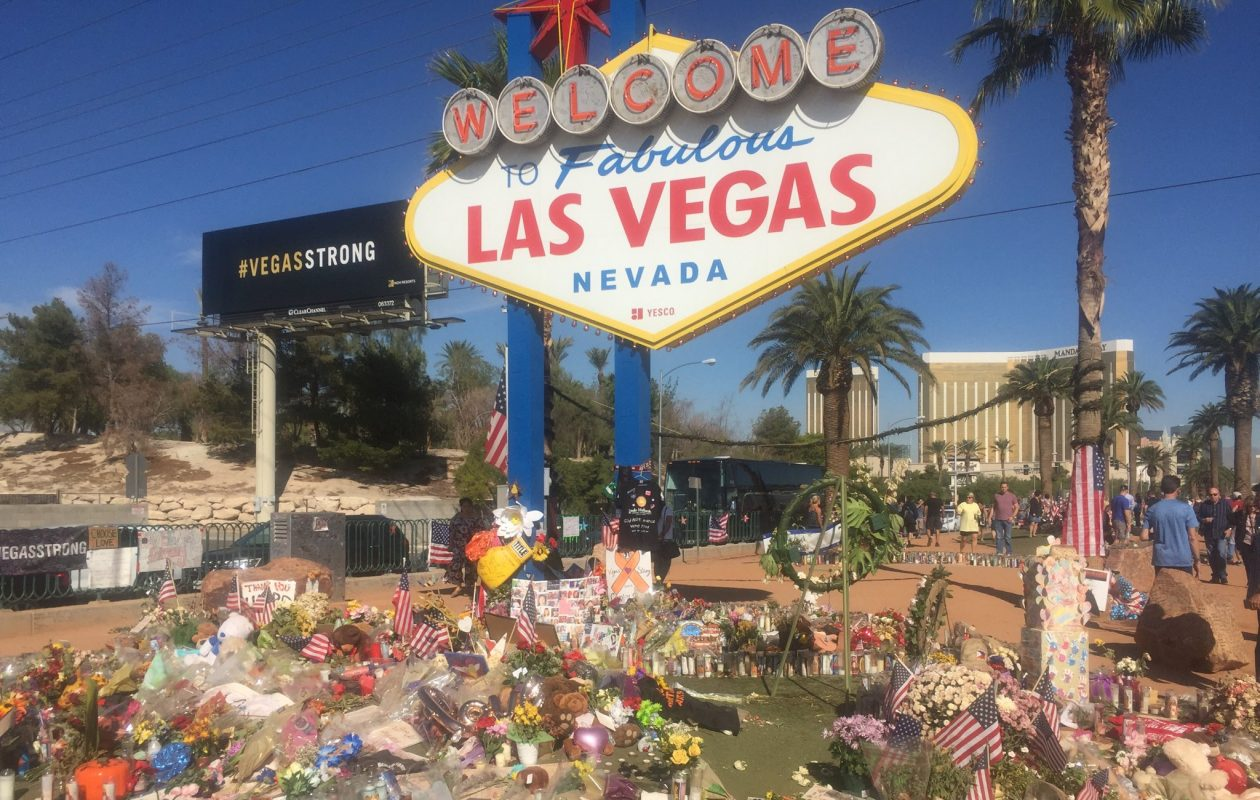Flowers and other momentos have been left at the foot of the welcome sign in the wake of the Oct. 1 Las Vegas shooting. (Mike Harrington/Buffalo News)