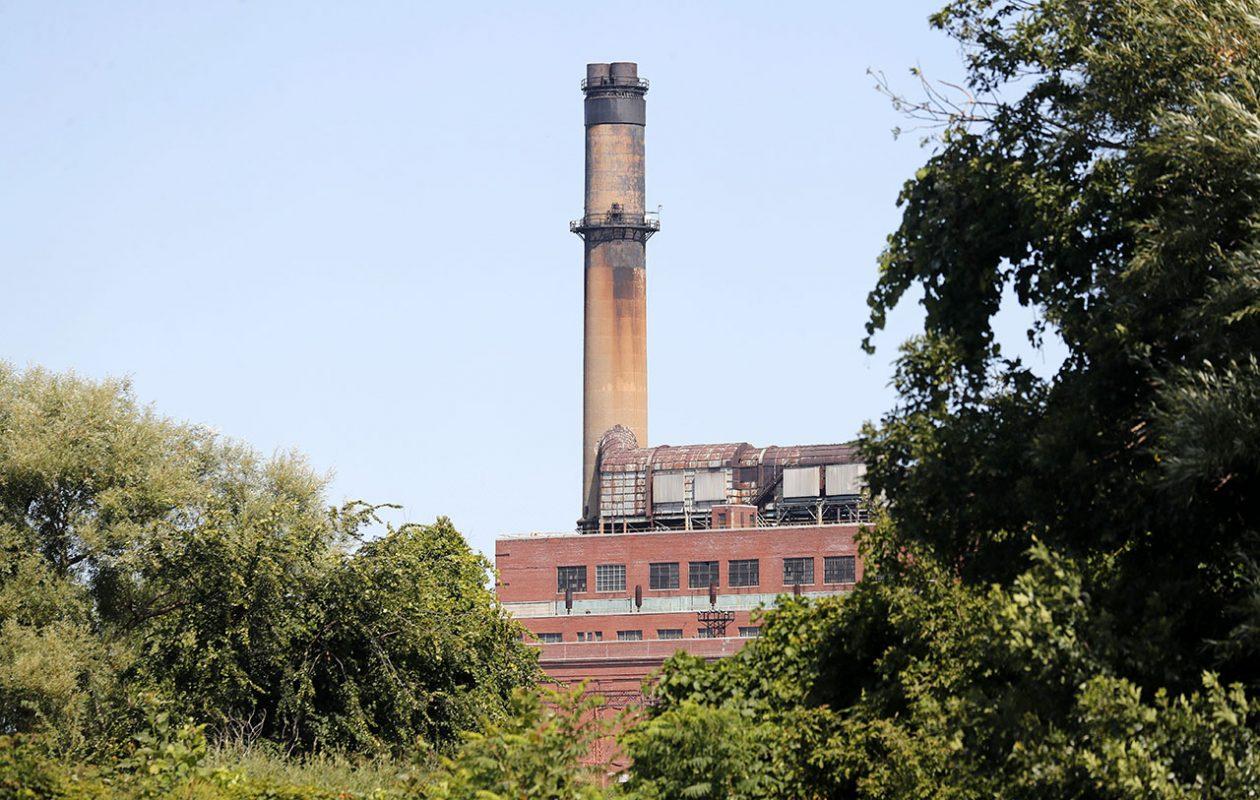 The shuttered Huntley Power Plant in the Town of Tonawanda looms over trees on Motor Island along the Niagara River. (Mark Mulville/Buffalo News)