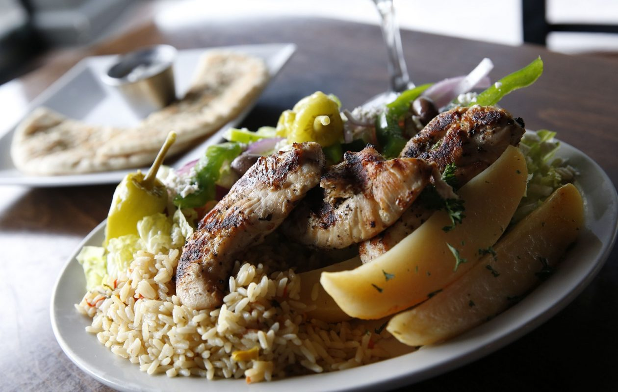 Acropolis OPA's chicken souvlaki dinner is made with rice, romaine, tomatoes, red onion, green peppers, olives, cucumbers, pepperoncini and feta with pita and tzatziki sauce. (Sharon Cantillon/Buffalo News)