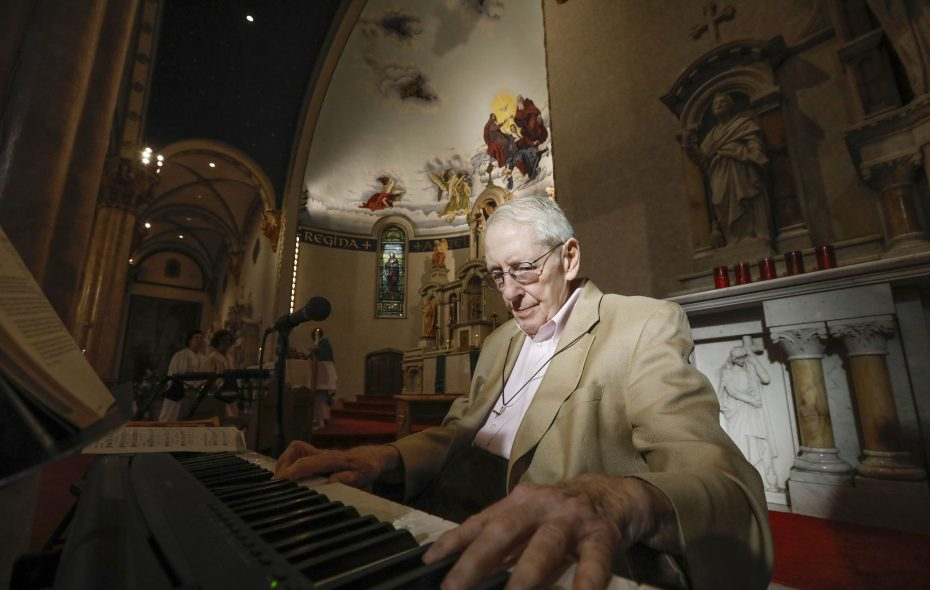 His arthritis prevents him climbing upstairs to the organ loft these days, so Bob Chambers plays the keyboard during Mass at  Holy Angels Catholic Church, where he has been the organist for more than 70 years.  (Derek Gee/Buffalo News)