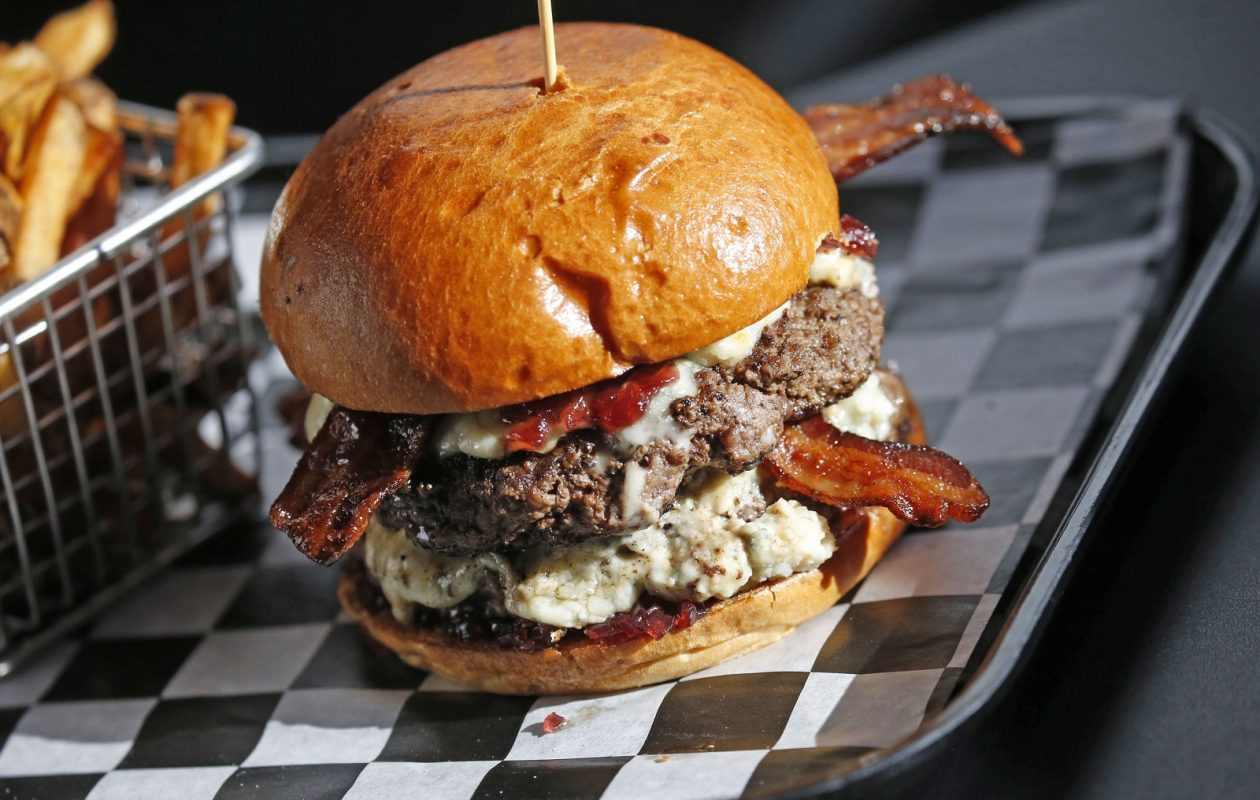 Juicy Burger Bar's Chuck Norris Roundhouse double is a black-and-blue burger 'to the FACE,' red onion jam with blue cheese and bacon. (Robert Kirkham/Buffalo News)