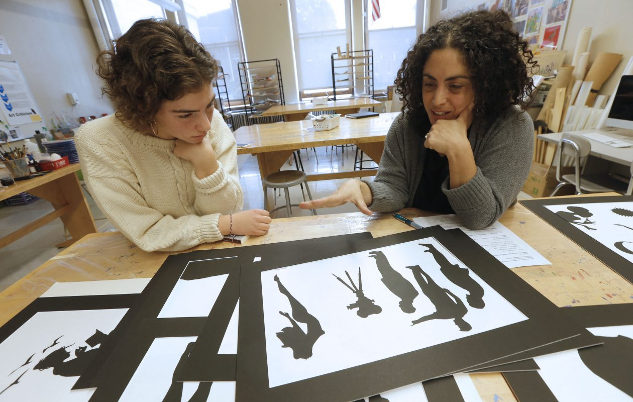 Sophomore Lily Lettieri, left, discusses her artwork with art teacher Becky Moda. Students at City Honors School participated in an art project based on the work of Kara Walker in advance of the 50th anniversary of the Rev. Martin Luther King Jr.'s 1967 speech in Kleinhans Music Hall. (Robert Kirkham/Buffalo News)