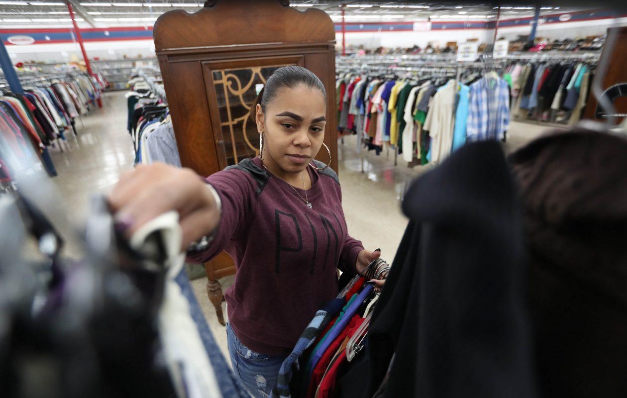 Amvets Thrift Store employee Shermara Jimenez brings out a rack of merchandise. (Sharon Cantillon/Buffalo News)