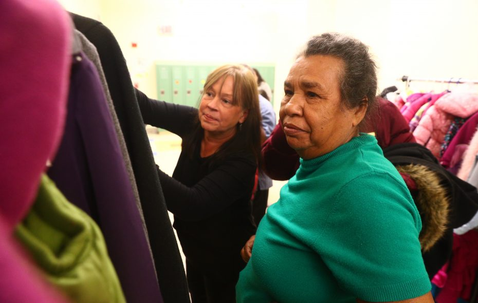 Kim Meissner, left, helps Rosa Negron try on a coat at Herman Badillo Bilingual Academy on Saturday, Nov. 18, 2017. Negron, of Juncos, Puerto Rico, came here recently to join her daughter Zuleyka Ortizo. Meissner has been organizing donation efforts to help families who came to Buffalo from Puerto Rico after Hurricane Maria. (John Hickey/Buffalo News)