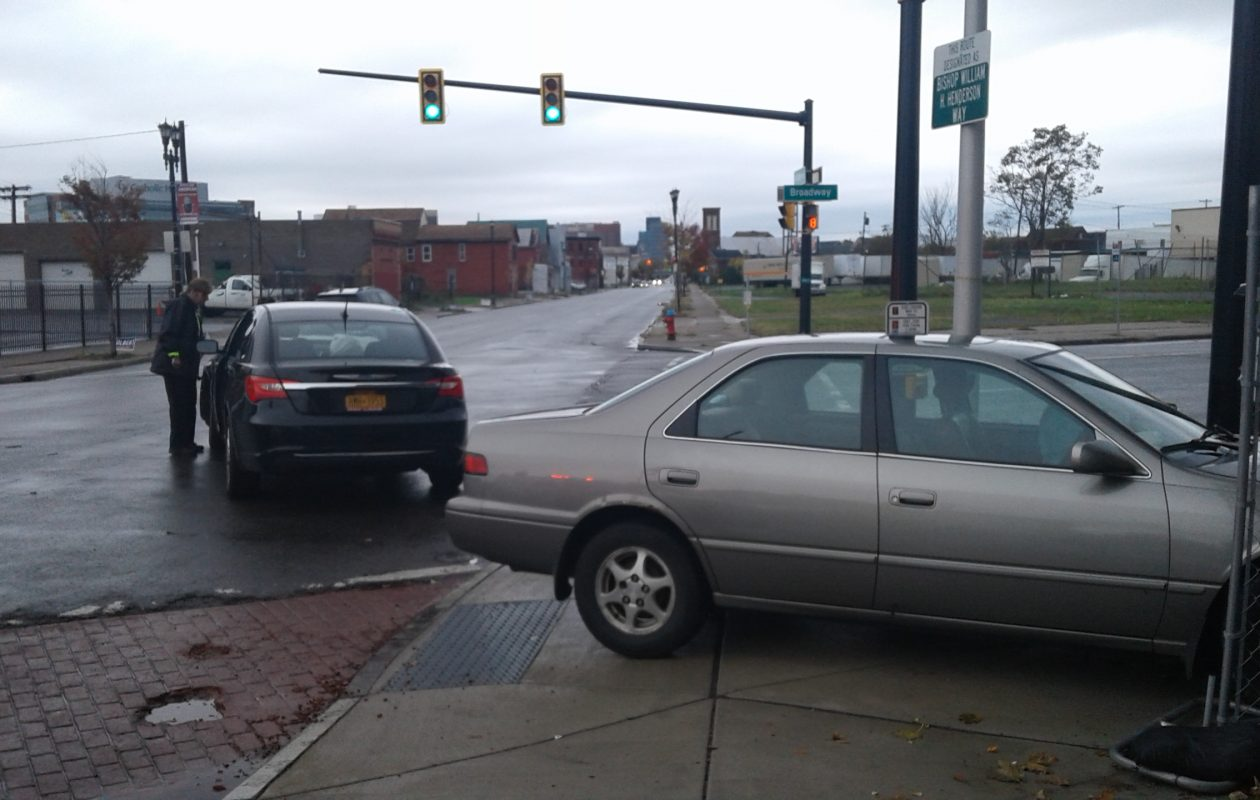 A Buffalo police officer checks a vehicle at the scene of a crash at Michigan Avenue and Broadway Nov. 5, 2017. (Thomas J. Prohaska/The Buffalo News)