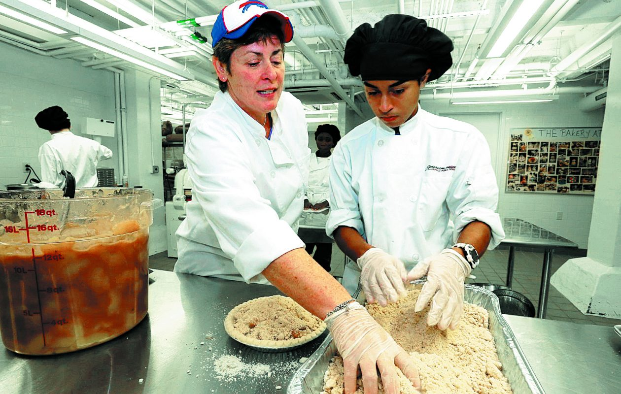 A News file photo shows bakery instructor Donna Emmert helping student Steven Cruz prepare an apple pie for  Emerson School of Hospitality's annual Thanksgiving pie sale. (John Hickey/Buffalo News) News)