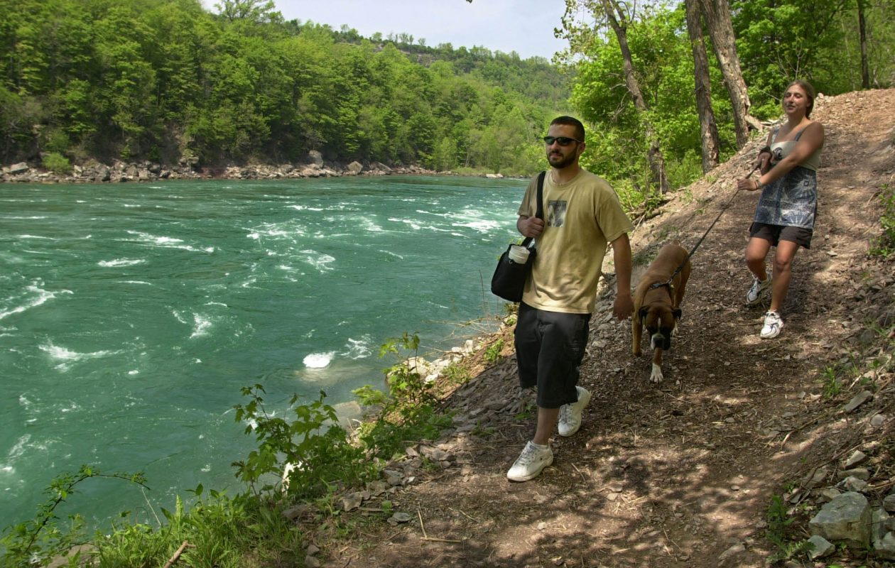 Rick Stanton and Amie Andres walk their dog, Otis, along the Onglala Trail at the base of the Niagara River Gorge between the Devil's Hole and Whirlpool Rapids visitor sites.  (2013 file photo / The Buffalo News)
