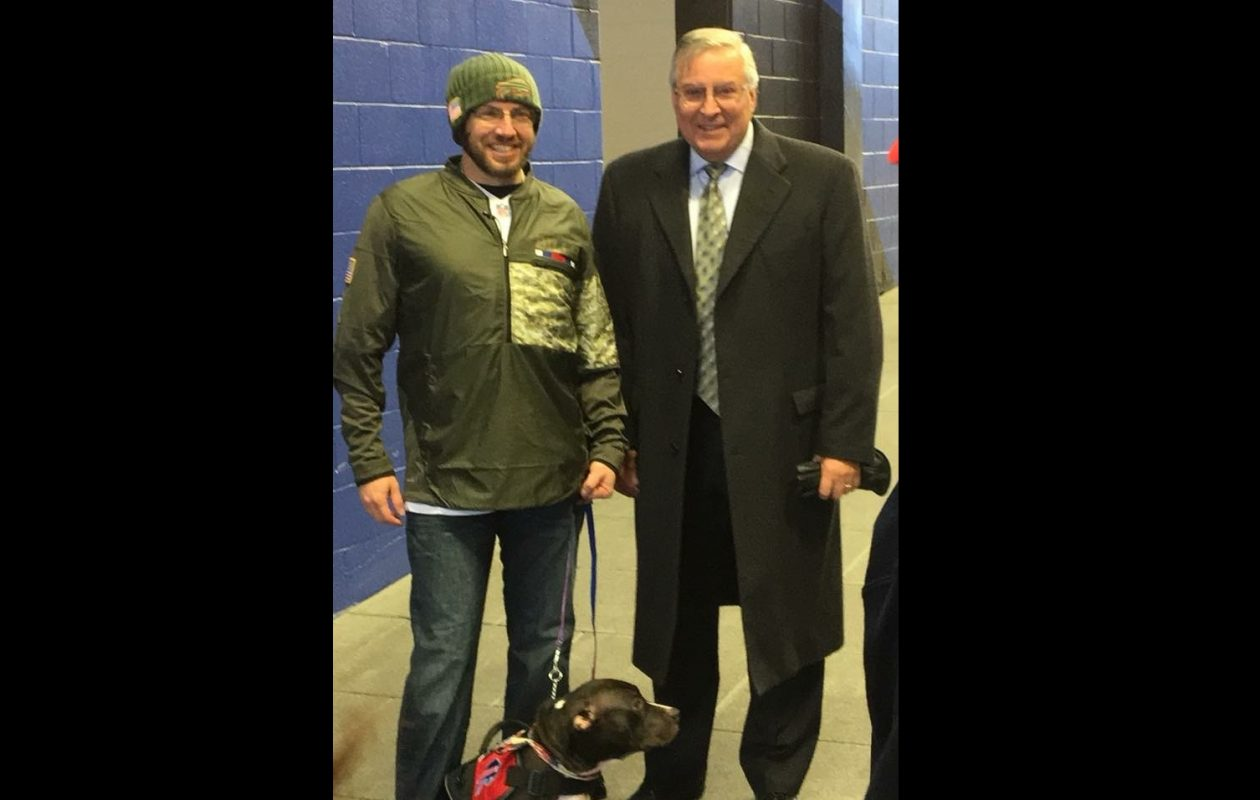 Buffalo Bills owner Terry Pegula, right, presented retired Master Sgt. James Kozma with Rebel, a service dog, at Sunday's game. (Photo courtesy of James Kozma)