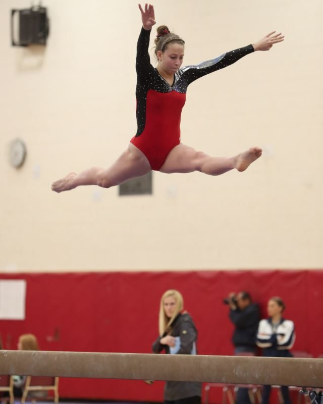 Makenzie Castiglione of Lancaster competes on the balance beam in the Section VI girls gymnastics championships at Clarence High School. (Sharon Cantillon/Buffalo News)
