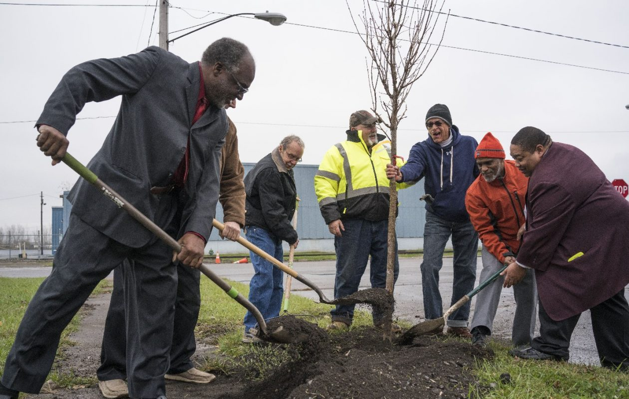 A group gathers to help plant the first of the trees to beautify the neighborhood in honor of the people who died in the Moonglow Hotel fire 60 years ago. From left, they are Charles McCreary, Ron Anderluh, Dan Davis, City Forester Joe Urso, Bill Bradberry, the Rev. Raymond Allen and County Legislator Owen Steed.  (Derek Gee/Buffalo News)
