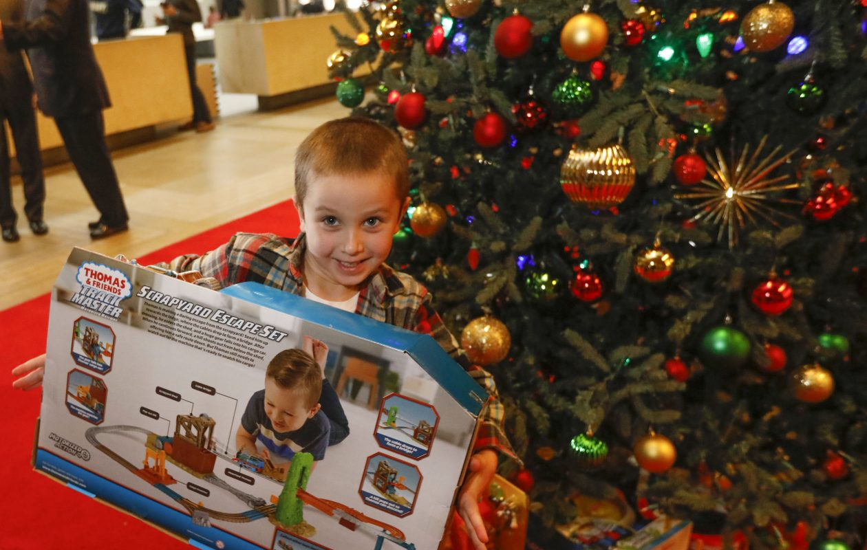 Houghton Academy kindergarten student Owen Geiger, 5, helps place presents under the Christmas tree during the kickoff of the annual News Neediest drive in the lobby of The Buffalo News, Friday, Nov. 17, 2017.  (Derek Gee/Buffalo News)