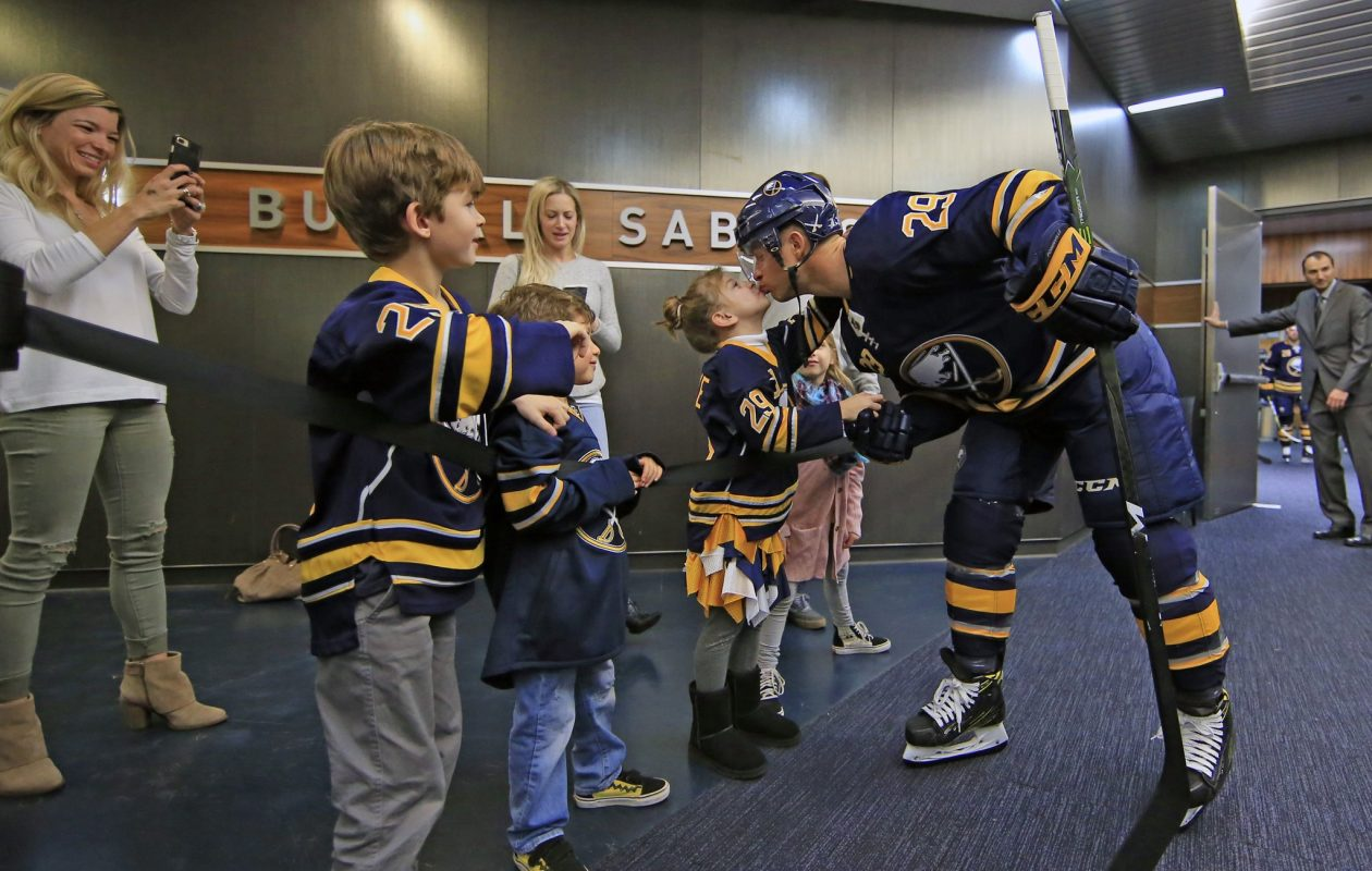 Jason Pominville got a good-luck kiss from his daughter, Kaylee, as wife Kim took a picture at left before the Sabres took the ice for a game last season. (Harry Scull Jr./News file photo)
