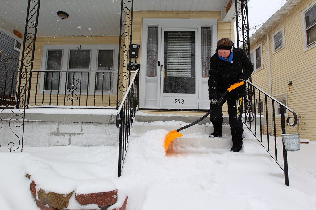 Brianna Alley clears the steps to her home on Ontario Street in Buffalo Tuesday, March 14, 2017.       (Mark Mulville/Buffalo News)