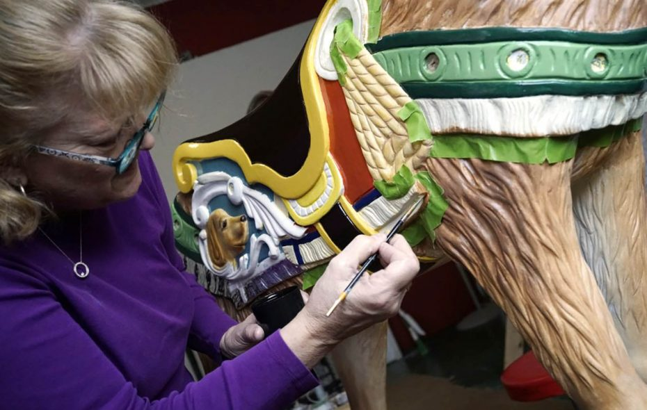 Kathy Kwiatkowski works on fine detail, while painting the deer amid the newly restored antique horses that will be used on the carousel to be installed at Canalside in 2019. (Derek Gee/Buffalo News)