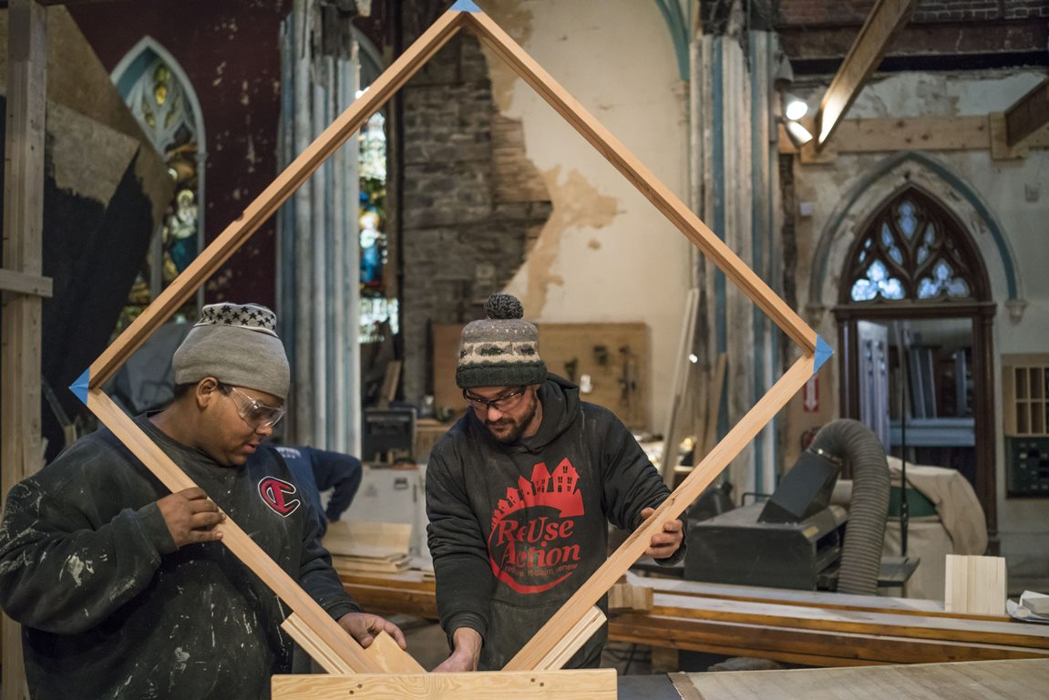 Christopher Tyes, left, and lead instructor Danny Solomon use a table saw to cut notches in a frame Tyes is building while participating in a program called Society for the Advancement of Construction Related Arts at Assembly House – the former Immaculate Conception Catholic Church. (Derek Gee/Buffalo News)