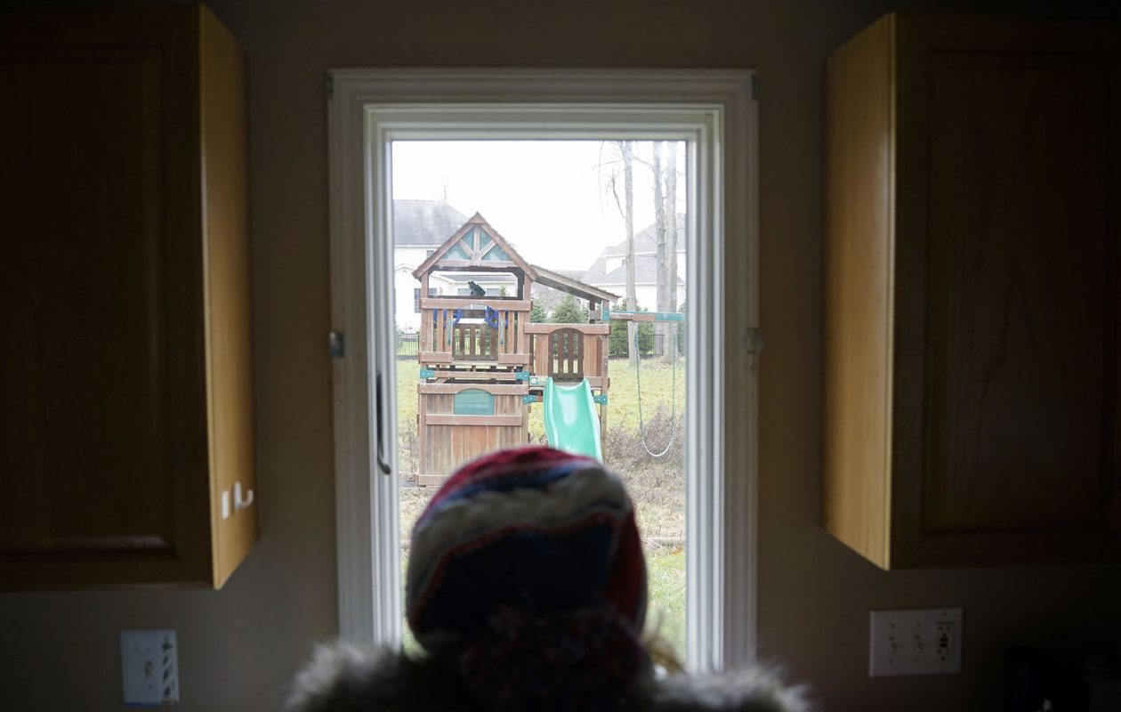Rosemarie Peterson looks out of the window of the home in Amherst that her husband, Donald, remodeled for their family. She and her daughters fled the house out of fear for their safety as Donald struggled with and eventually, she believes, died from an opioid addiction. (Derek Gee/Buffalo News)