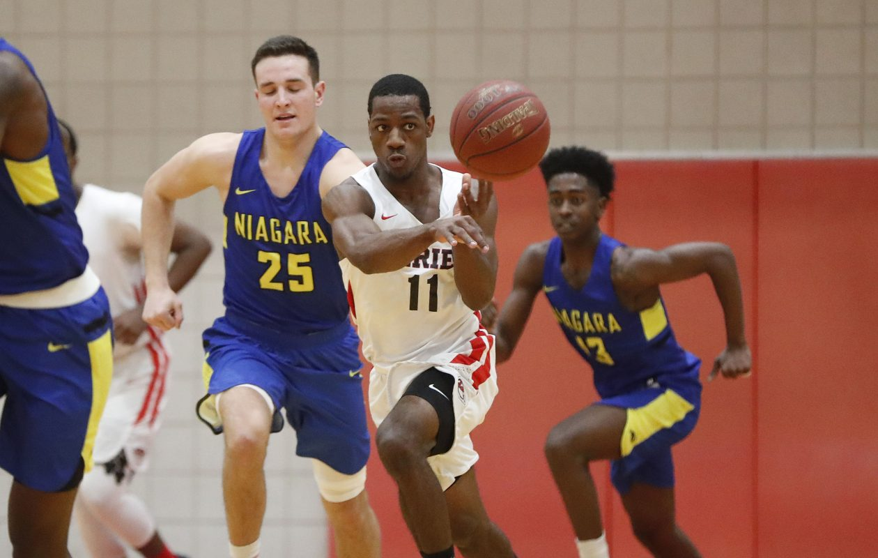 ECC's Shakur Harris dishes a pass on a rush in the first half of the game with NCCC at the Flickinger Center in Buffalo Wednesday (Mark Mulville/Buffalo News)