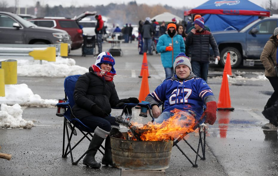 Colleen and Patrick Mayer stay warm by a fire before the game with the Miami Dolphins at New Era Field. (Mark Mulville/News file photo)
