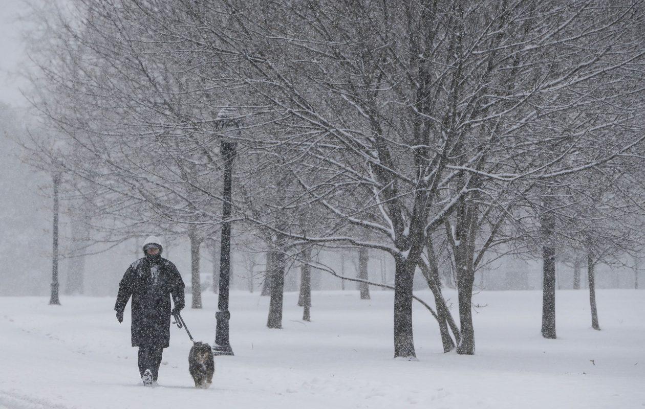 Tim Wadkins and his dog Sydney walk through the winter wonderland at Delaware Park as heavy snow falls, Saturday, Dec. 23, 2017.  (Derek Gee/Buffalo News)