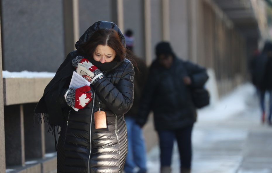 Mary Ziolkowski covers her mouth after she walks along Main Street in downtown Buffalo on her lunch break, Wednesday, Dec. 27, 2017. (Sharon Cantillon/Buffalo News)