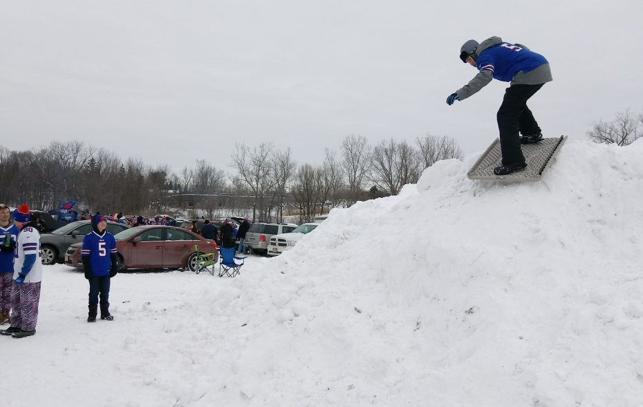 """One Bills fan tried to """"snowboard"""" down one of the slopes in a parking lot. (Luke Hammill/Special to The News)"""