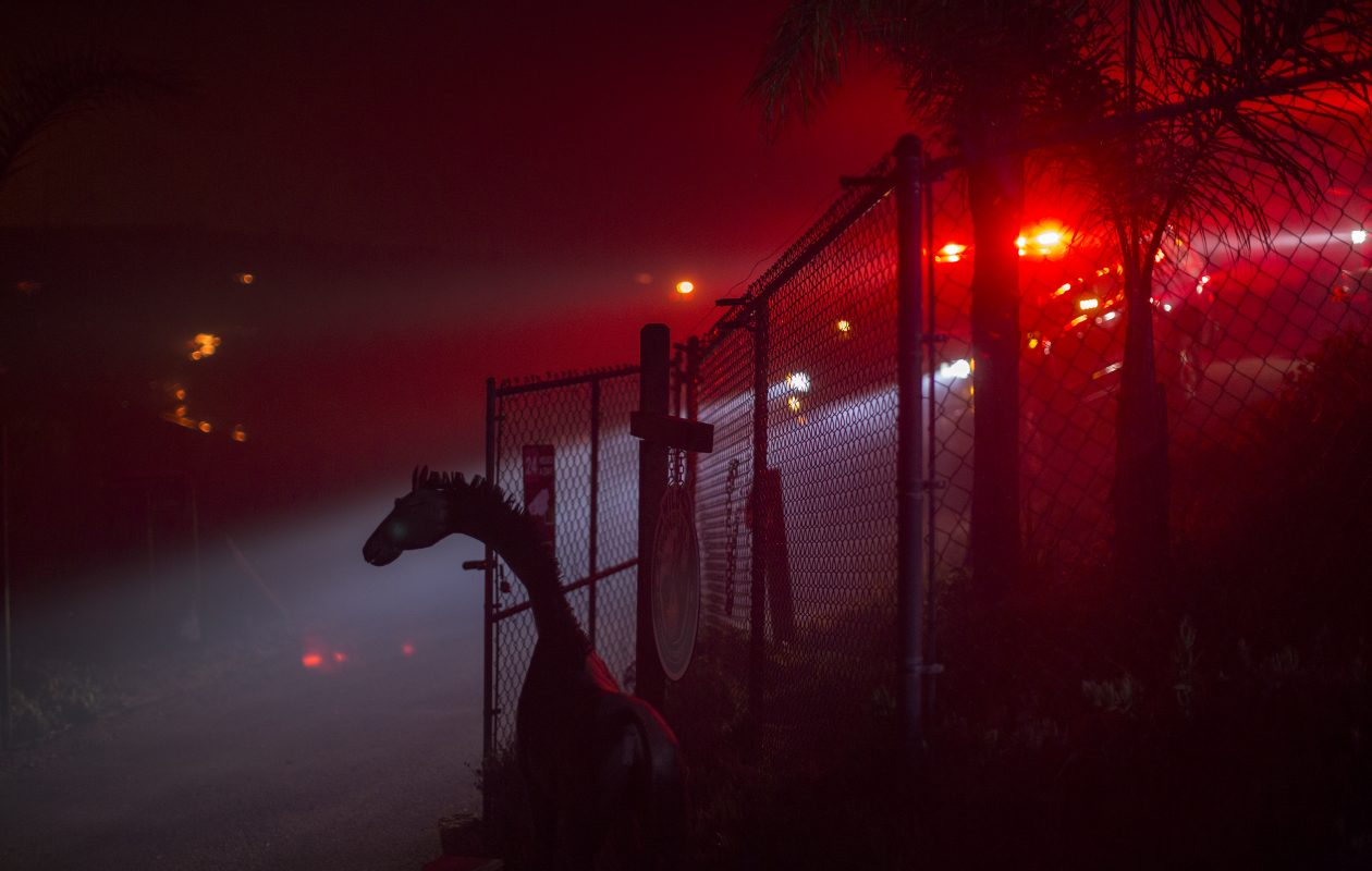 The lights of a firetruck shine behind a metal animal sculpture at the Lilac Fire on December 7, 2017 near Bonsall, California. Strong Santa Ana winds are pushing multiple wildfires across the region, expanding across tens of thousands of acres and destroying hundreds of homes and structures.  (Photo by David McNew/Getty Images)