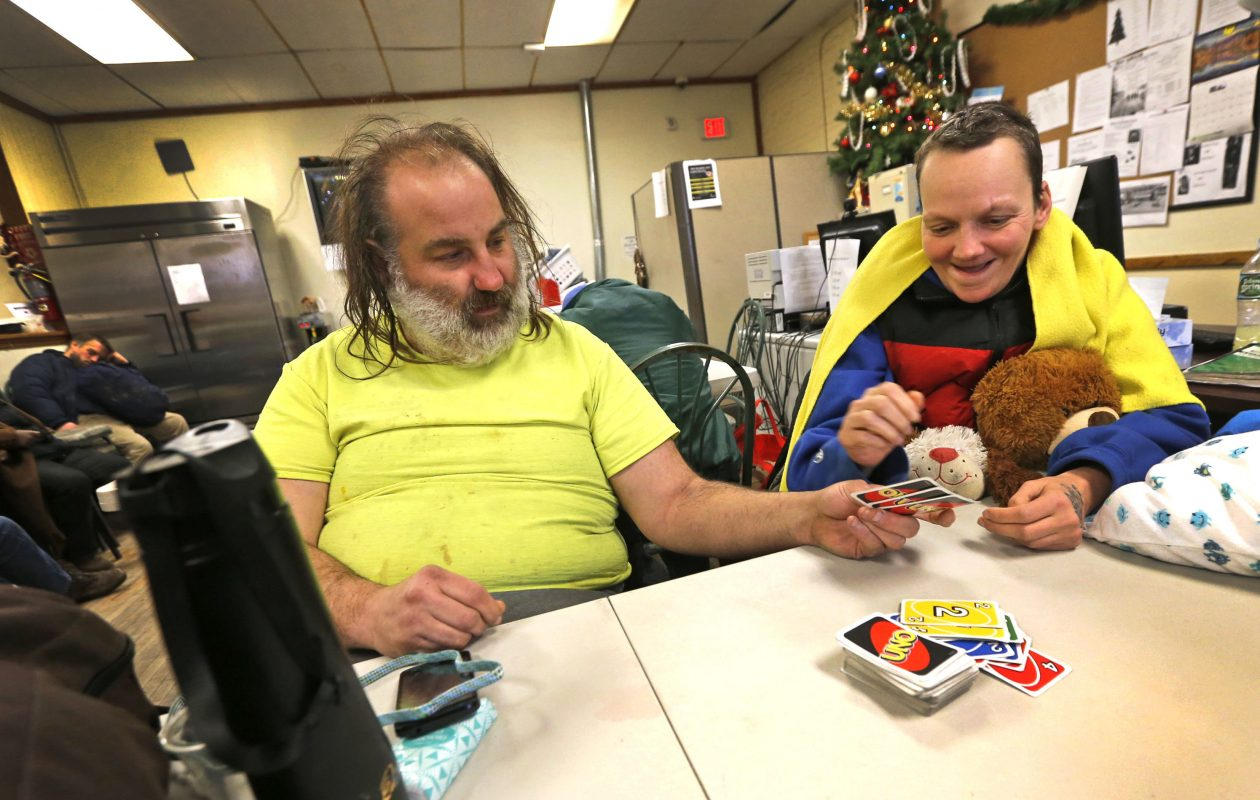 Homeless couple William, left,  and Rebecca Brain pass the time playing card games at the Harbor House at 241 Genesee St. The center  opened its doors during our recent cold snap and Code Blue status for those on the streets.   (Robert Kirkham/Buffalo News)