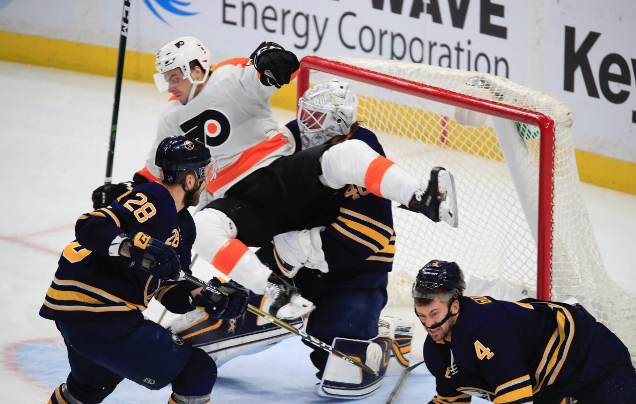 The crease was a busy place Friday with Philadelphia's Scott Laughton joining Sabres goaltender Robin Lehner, forward Zemgus Girgensons (28) and defenseman Josh Gorges (4). (Harry Scull Jr./Buffalo News)