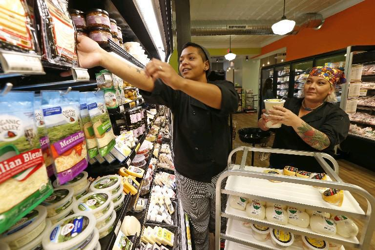 Meagan Heldwein, left, and Jamie Zynda, both deli managers, stock cheese and dairy items at the East Aurora Co-Op, which opened last summer. A group of volunteers is working to bring a similar cooperative market to Williamsville.