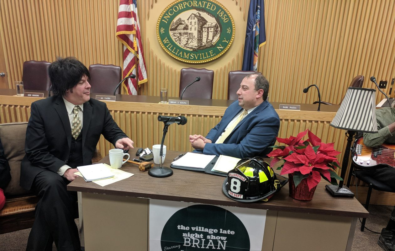 Williamsville Deputy Mayor Dan DeLano, left, chats with Mayor Brian Kulpa on Dec. 11, 2017, during Kulpa's final Village Board meeting, which was held in a talk show format.  (Photo provided by Village of Williamsville)