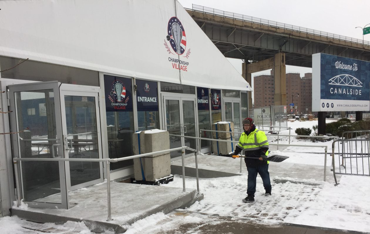 Anthony Turello of Buffalo Place shovels snow from in front of the Championship Village at Canalside, set up for the IIHF World Junior Championship taking place in Buffalo starting next week. (Aaron Besecker/Buffalo News)