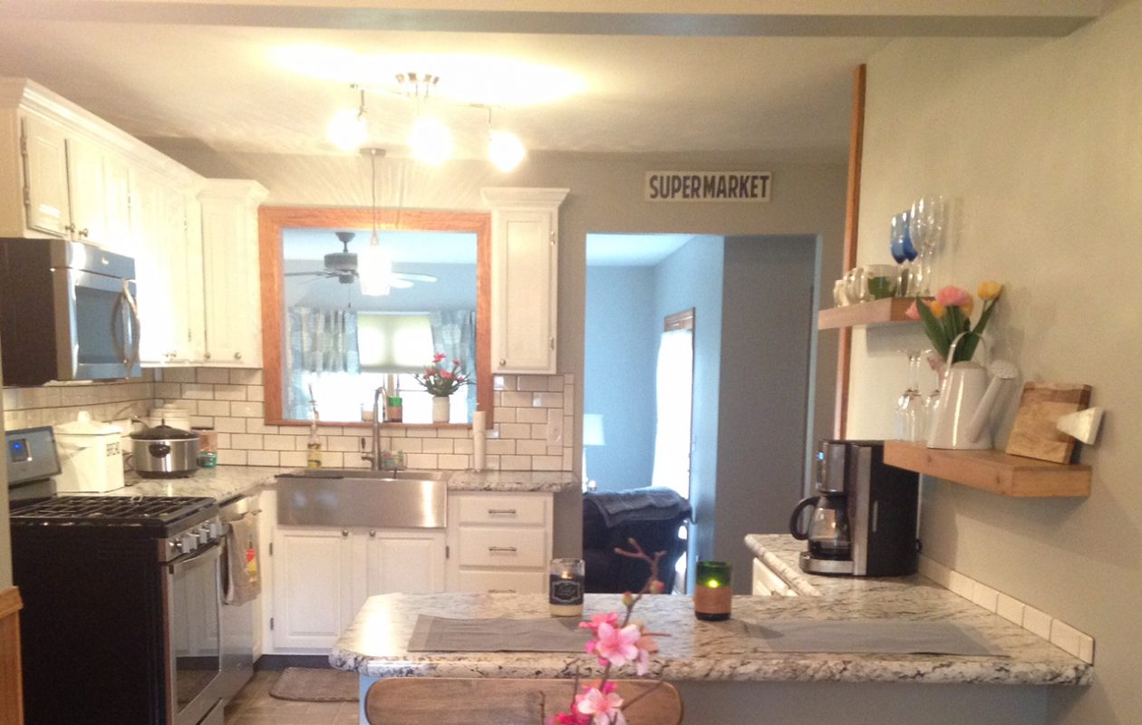 To update her kitchen, homeowner Jaime Wolniewicz had the cabinets painted white and added new laminate countertops, farmhouse sink and backsplash.