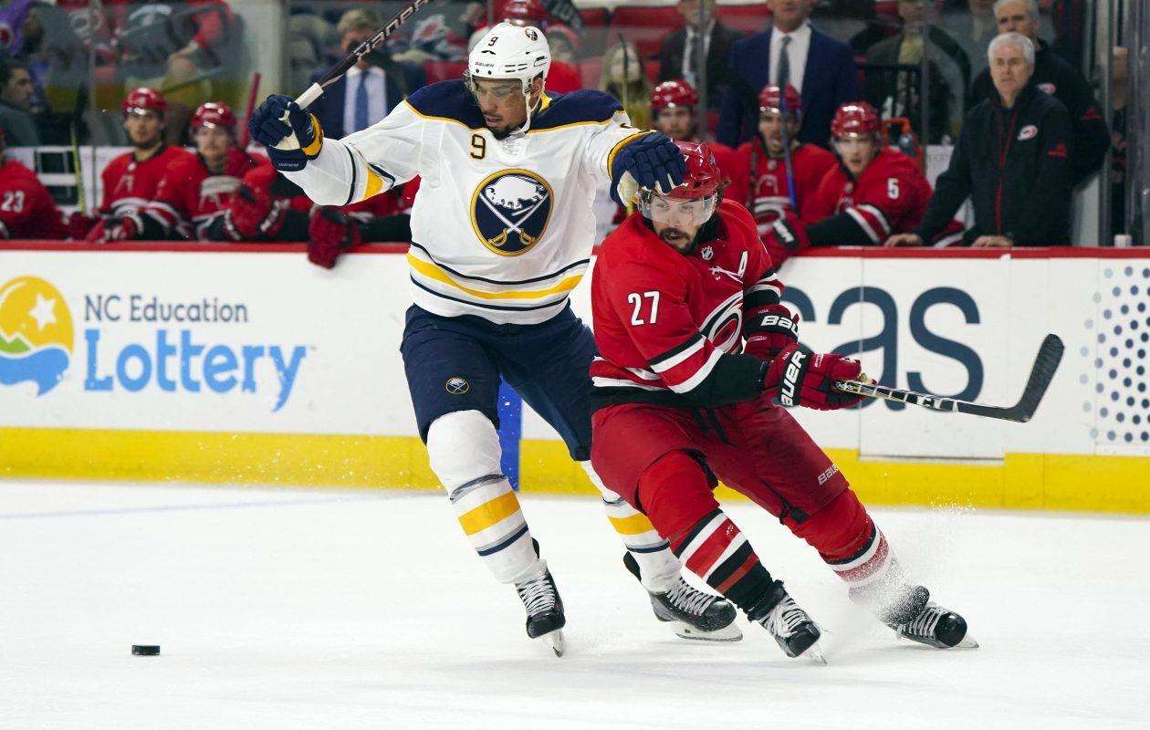 Evander Kane tries to work the puck past Carolina defenseman Justin Faulk (USA Today Sports).