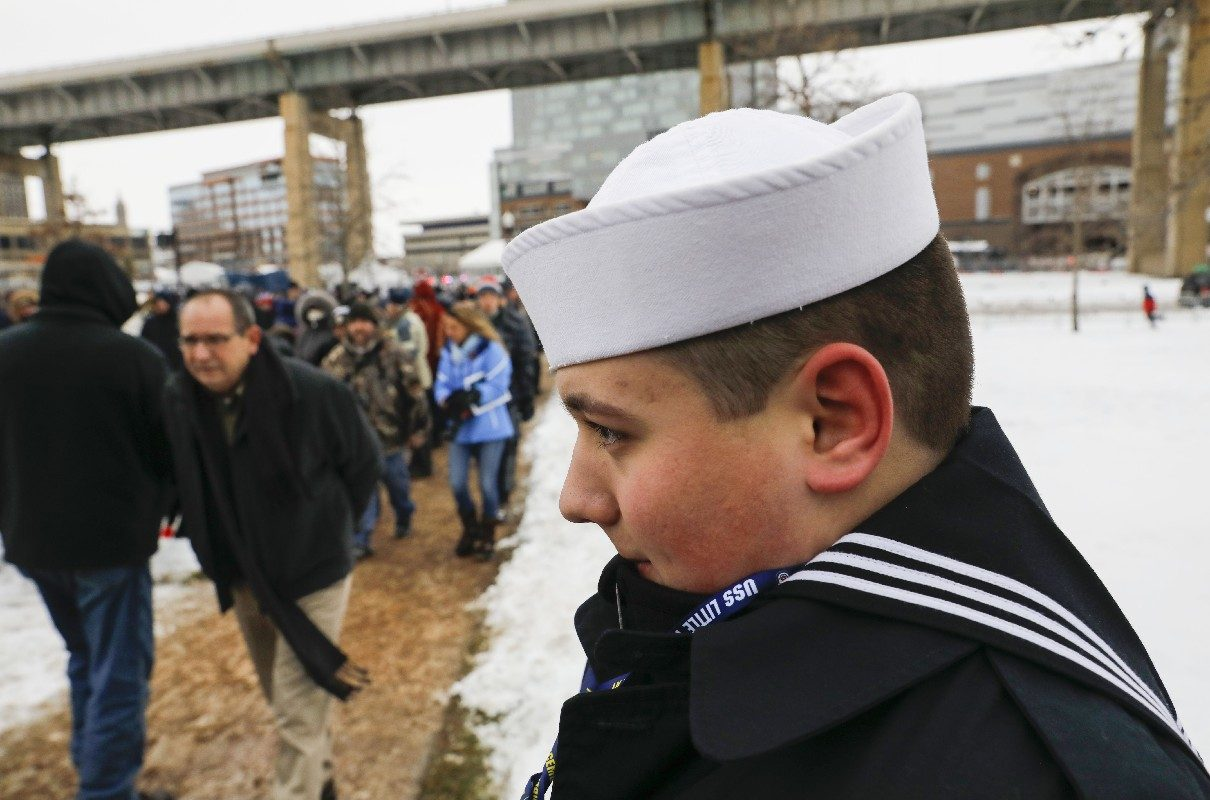 Cold-hardy U.S. Navy Sea Cadet Jacob Lawson of the City of Tonawanda assisted guests find their seats at the commissioning of the USS Little Rock at Canalside amid chilly conditions, and some snowflakes, on Saturday. (Derek Gee/Buffalo News)