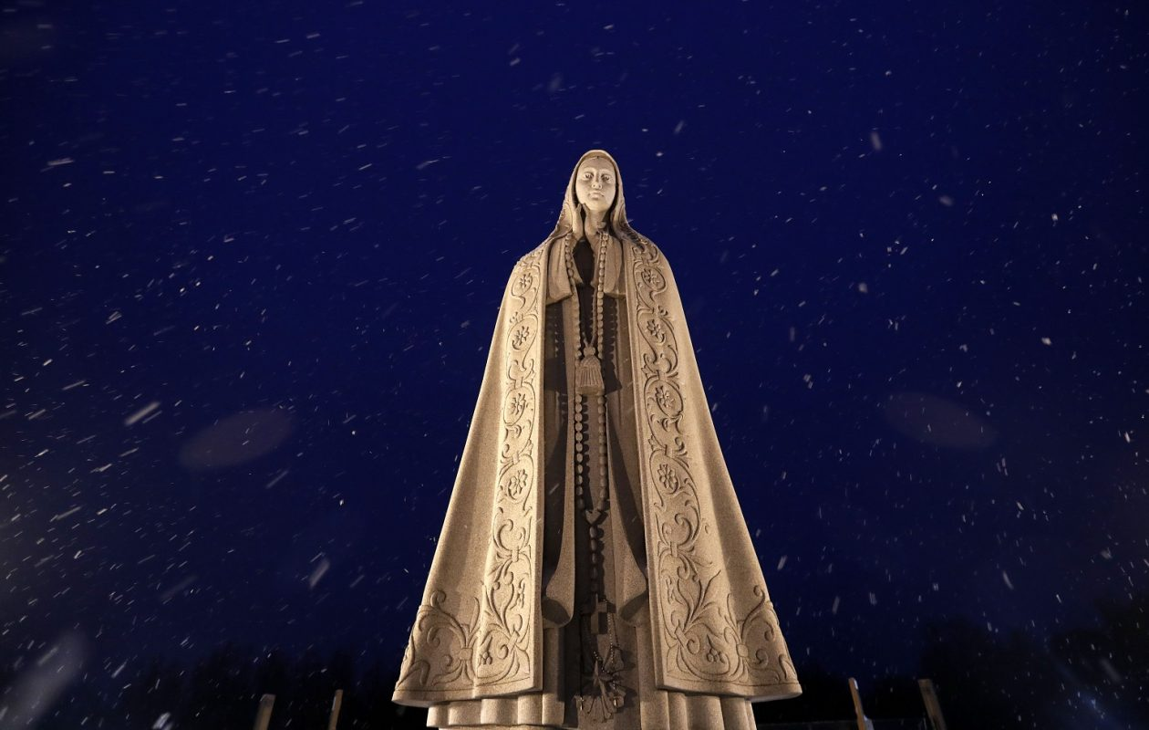 A stone statue of Our Lady of Fatima is lit in the falling snow on top the Ambulatory for the Festival of Lights at the National Shrine Basilica of Our Lady of Fatima. (Mark Mulville/Buffalo News)