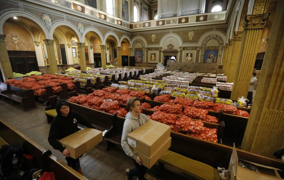 Food donations fill the pews at St. Luke's Mission of Mercy as supplies are gathered to make the 2,700 Thanksgiving meal bags that will be distributed.  Canisius High School sophomores Braeden Rottner, left, and Andrew Kissel help unload a truckload of donations, Thursday, Nov. 16, 2017.  (Derek Gee/Buffalo News)