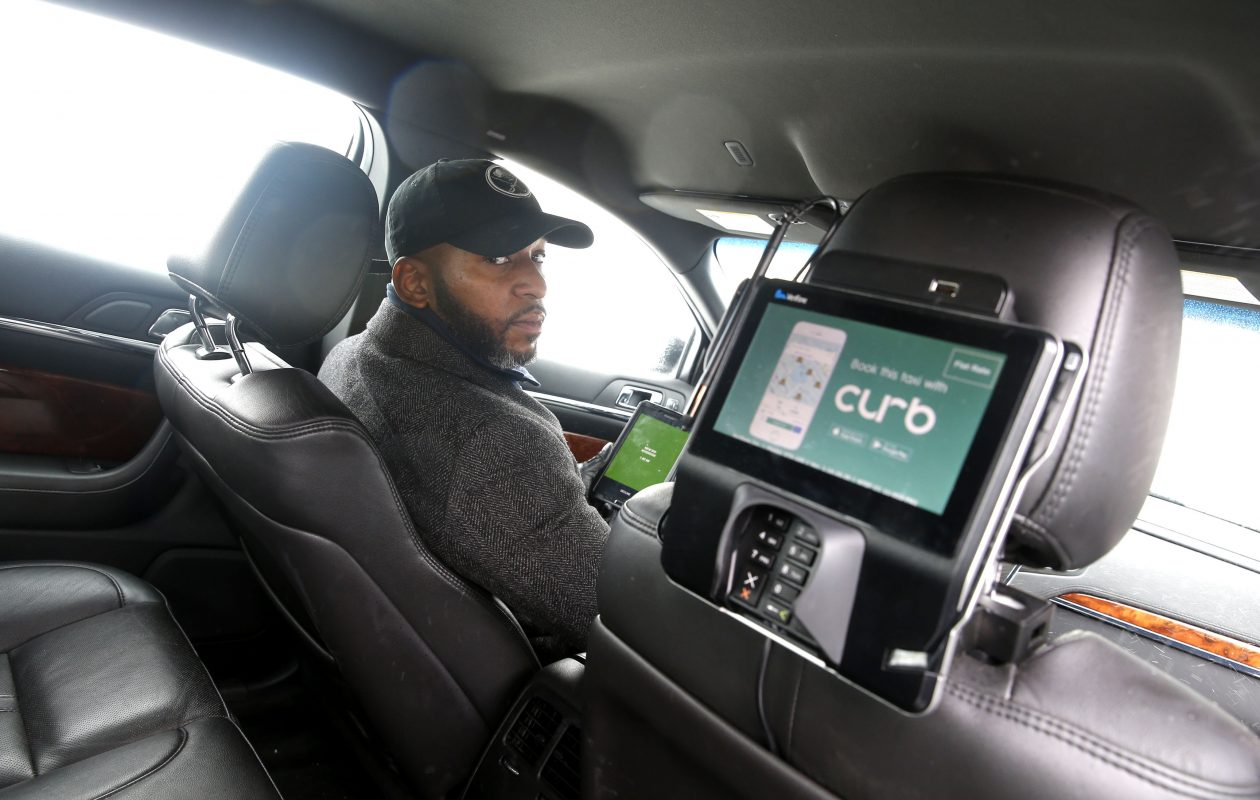 Liberty Yellow Cab executive class taxi driver Tyrell Adams at the wheel can easily communicate with passengers and explain how to use their 'Curb' app to pay for their fare.  (Robert Kirkham/Buffalo News)