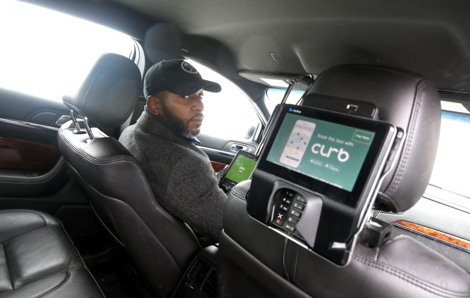 """Liberty Yellow Cab executive class taxi driver Tyrell Adams at the wheel can easily communicate with passengers and explain how to use their """"Curb"""" app to pay for their fare.  (Robert Kirkham/Buffalo News)"""