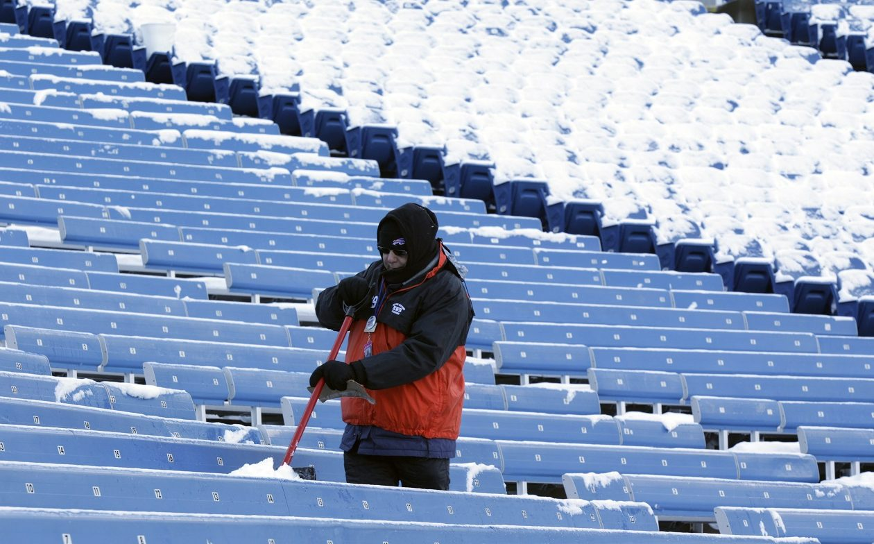 An usher removes snow prior to a game against the New York Jets in December 2012. {Harry Scull Jr./News file photo}