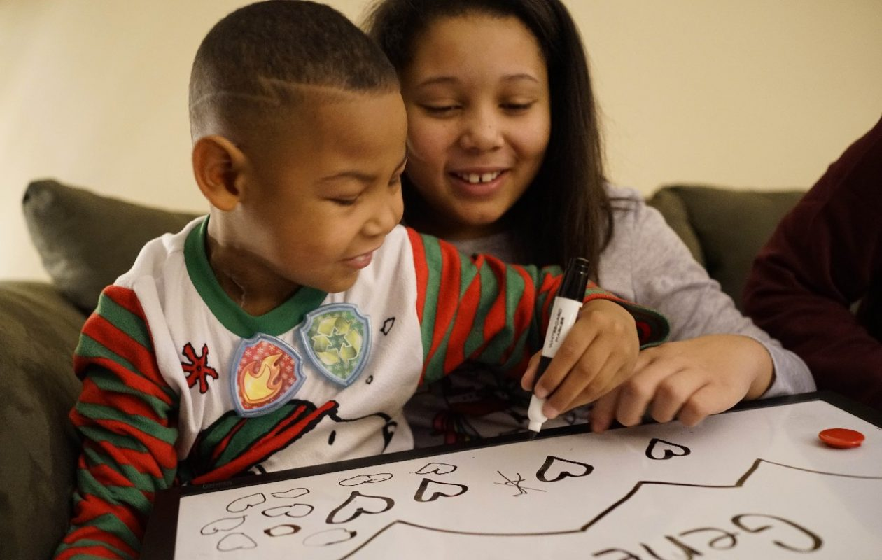 Gene Hilson III, 6, who is slated to have a life-saving kidney transplant in Pittsburgh on the day after Christmas, draws on a white board with his older sister, Noriana Ellison, 10, at their Niagara Falls home.  (Derek Gee/Buffalo News)