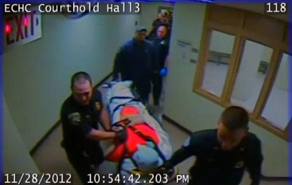 A still frame from surveillance video inside the Erie County Holding Center shows deputies and medics wheel inmate Richard Metcalf strapped to a gurney, face down with a pillow case covering his head on Nov. 28, 2012.
